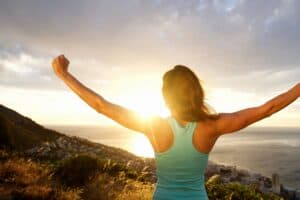 Woman standing on the top of a hill overlooking other hills. She has her arms up as if she just accomplished a big goal. The sun is setting.