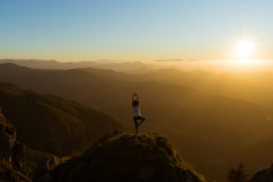 Image of a mountain range with a person standing on top of one. The sun is setting in the back.